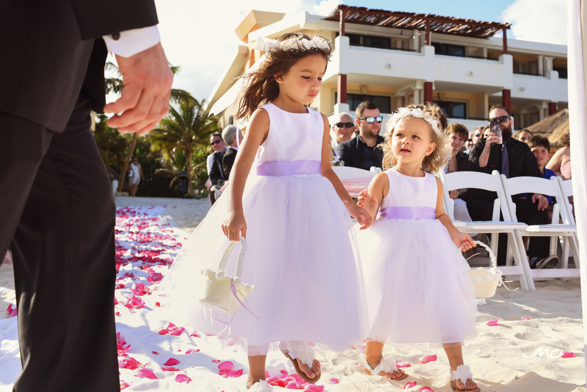 Lilac flower girls walk down the aisle at Now Sapphire, Mexico. Martina Campolo Wedding Photography