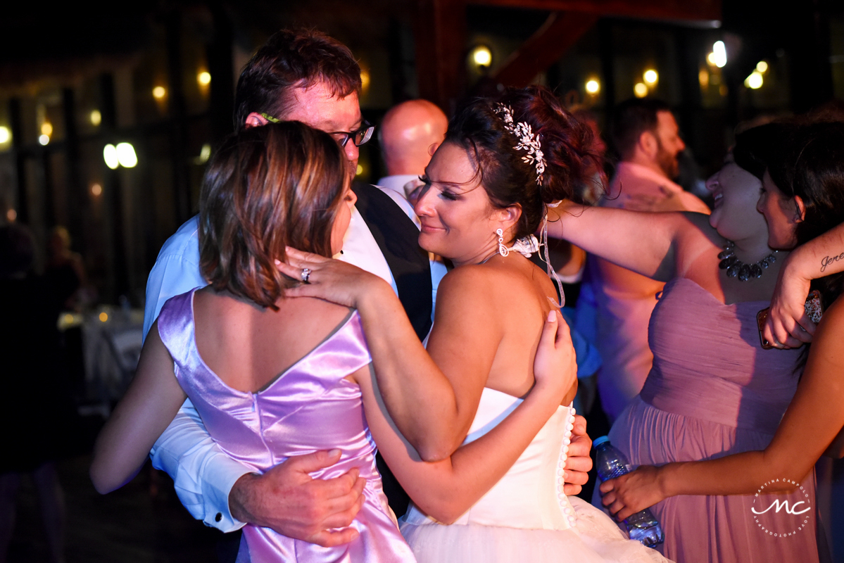 Bride and groom and daughter hug at Now Sapphire Wedding reception by Martina Campolo Photography